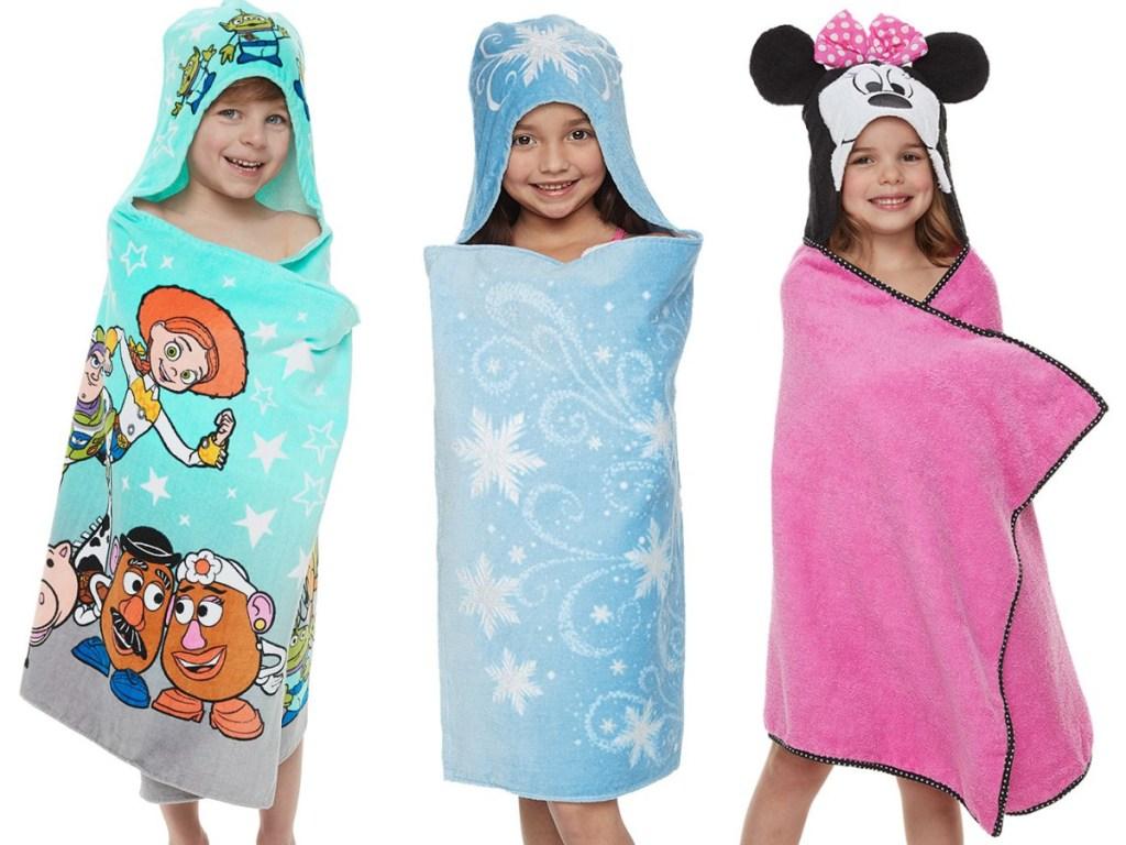 boy in Toy Story bath wrap, girl in blue Frozen bath wrap, and girl in pink Minnie Mouse bath wrap