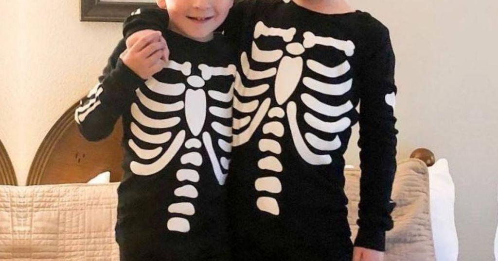 Two kids wearing glow in the dark skeleton pajamas