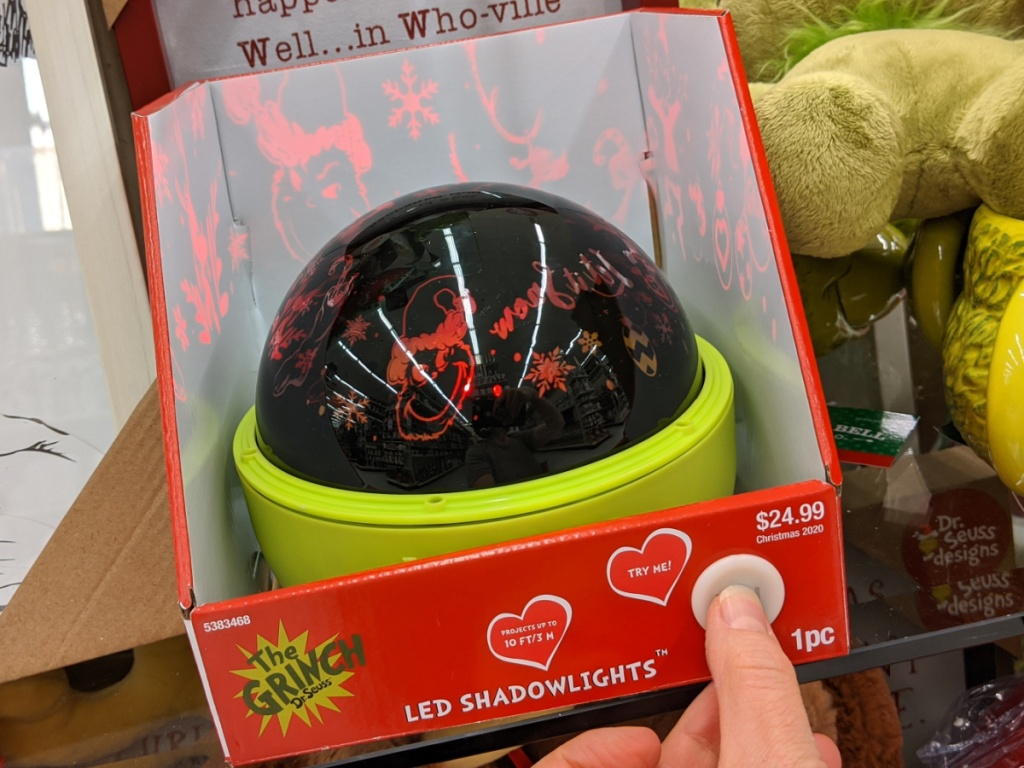 hand pressing button on Grinch light show projector in store