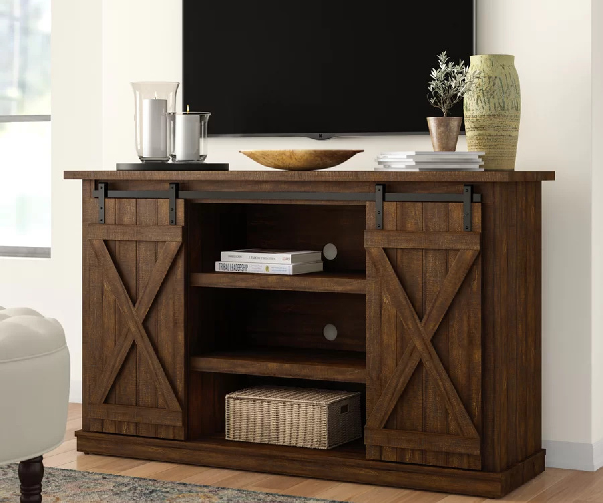 brown wood farmhouse style tv stand and tv in home