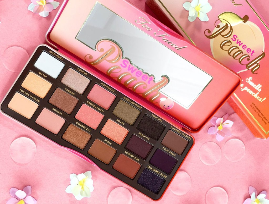 too faced sweet peach eyeshadow palette on pink background with flowers around it