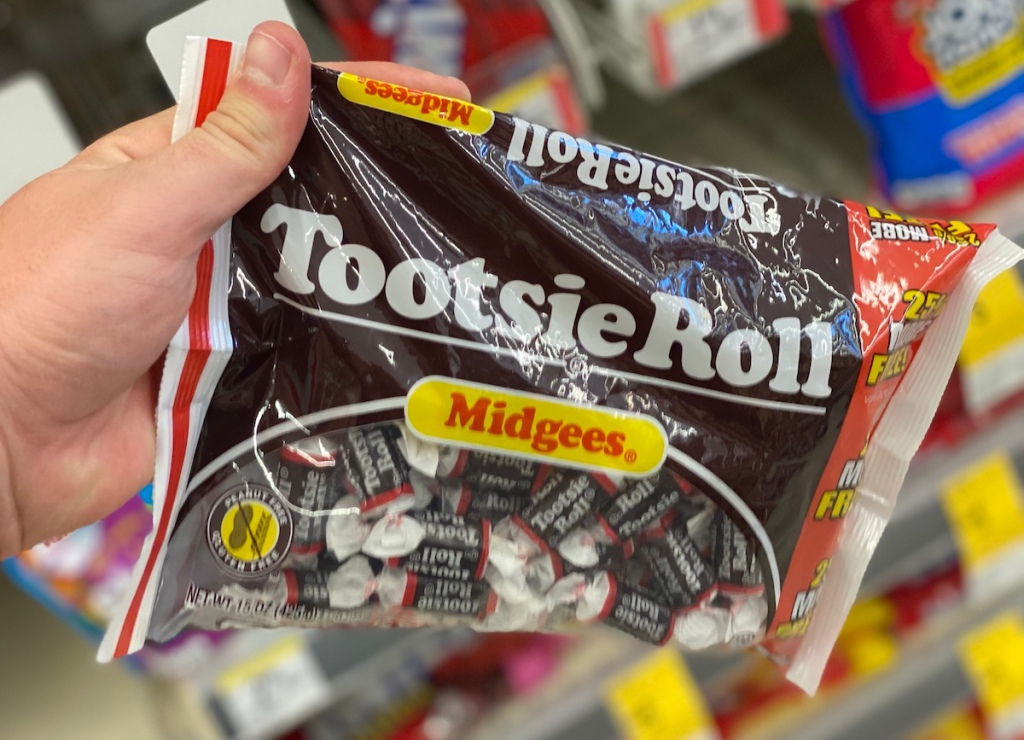 hand holding a bag of Tootsie Rolls