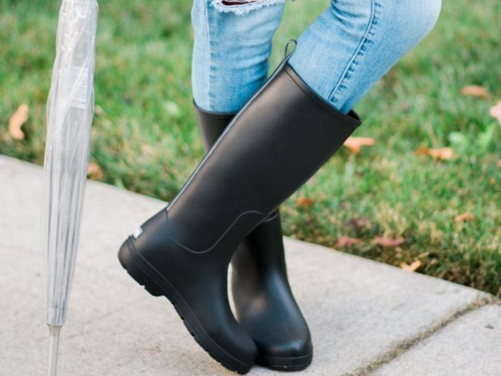 woman wearing tall rain boots with jeans and holding an umbrella