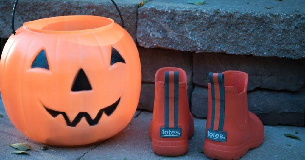 Totes Rain Boots for Kids next to orange pumpkin pail