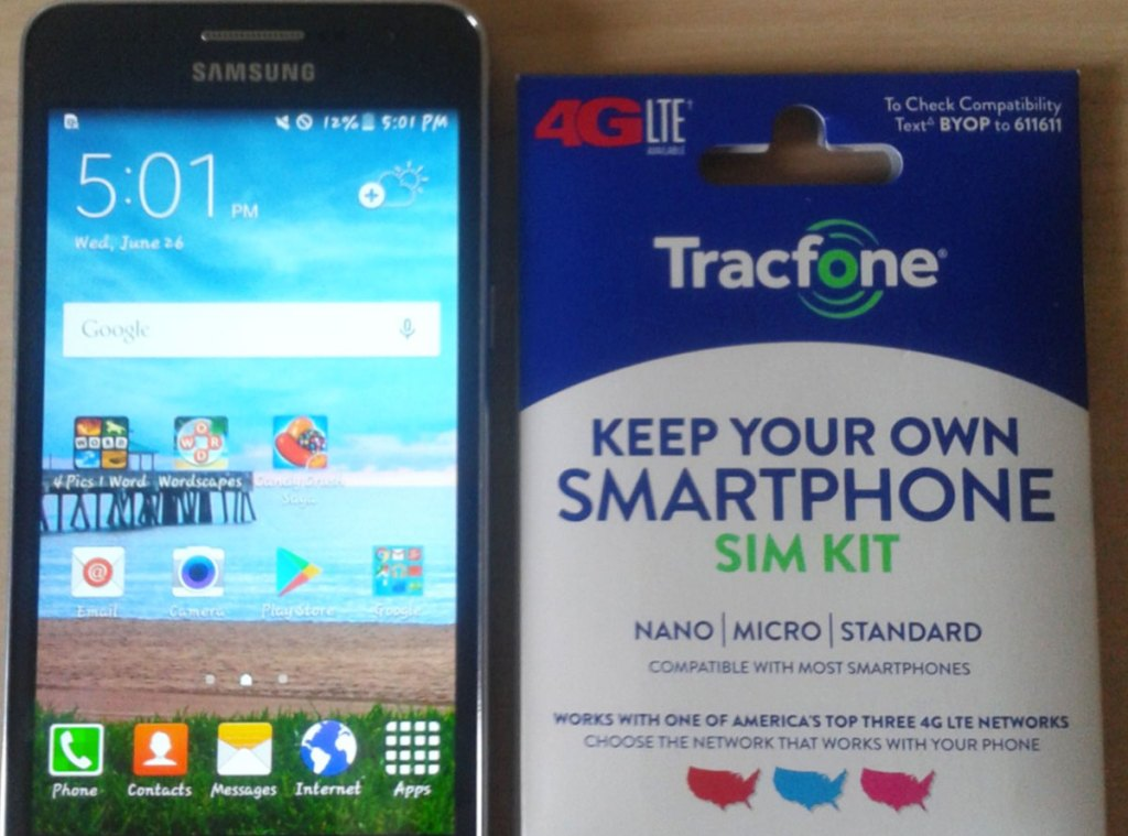 smartphone with Tracfone SIM kit next to it