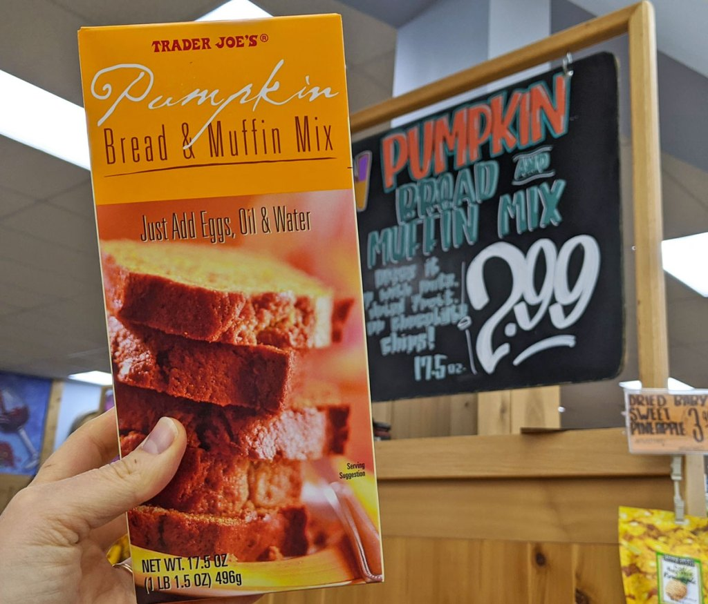 person holding up an orange box of pumpkin bread and muffin mix