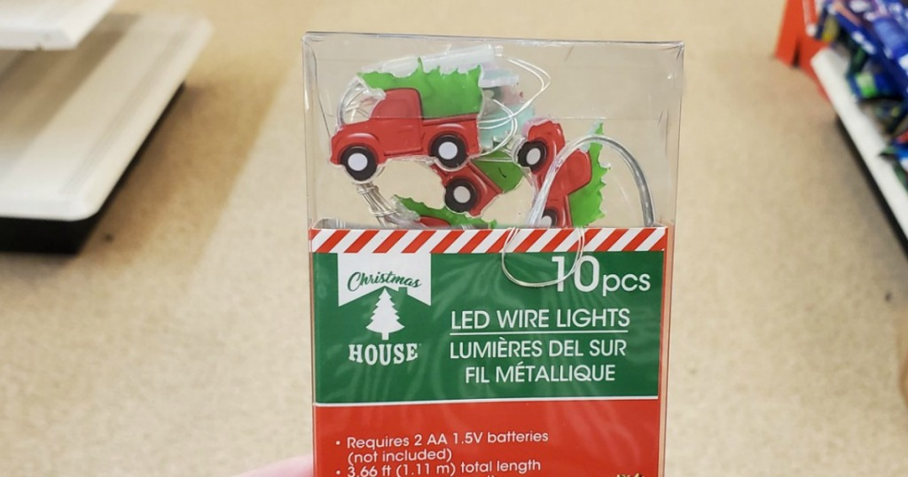 Hand holding up Truck shaped christmas lights in store