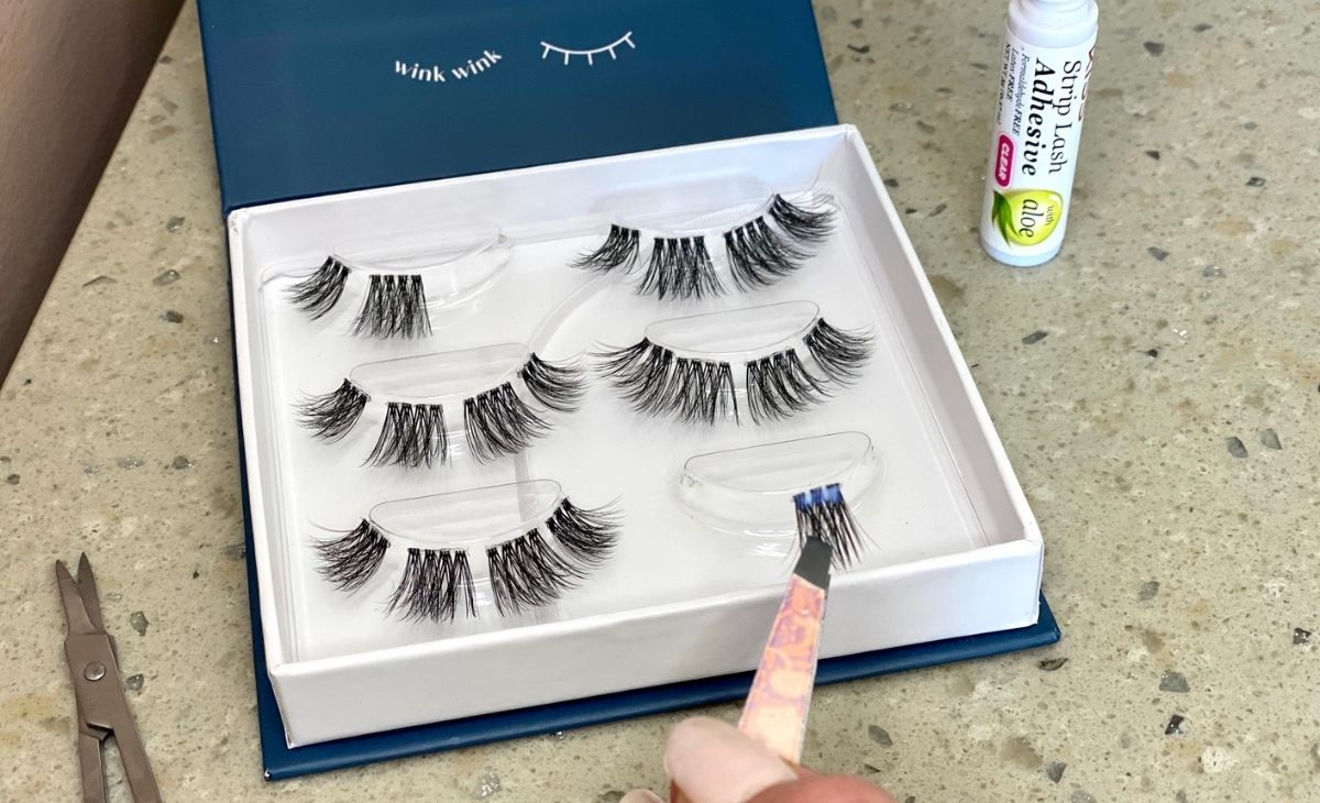 A box of false eyelashes on a counter and some tweezers with an eyelash piece on them