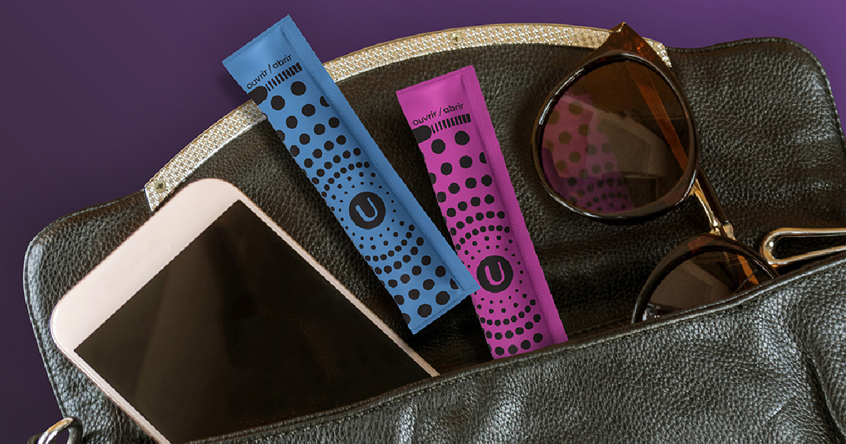 two packaged tampons, cellphone, and sunglasses in purse and purple background