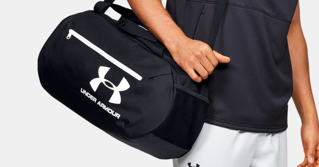 man carrying black duffle bag with white logo