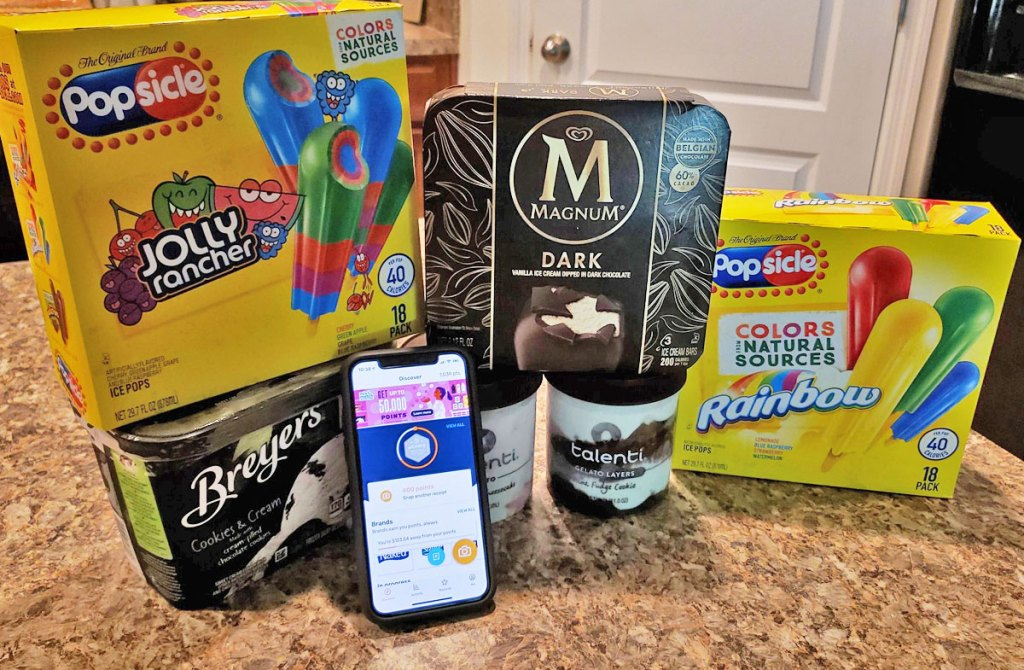 boxes of different ice cream brands on kitchen counter with smart phone showing fetch rewards app