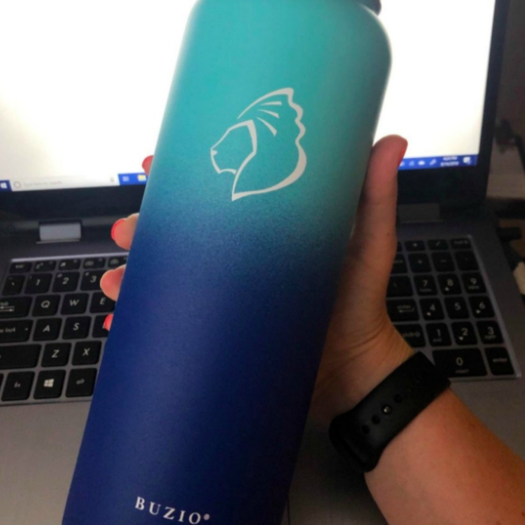 light blue and dark blue water bottle in front of a computer