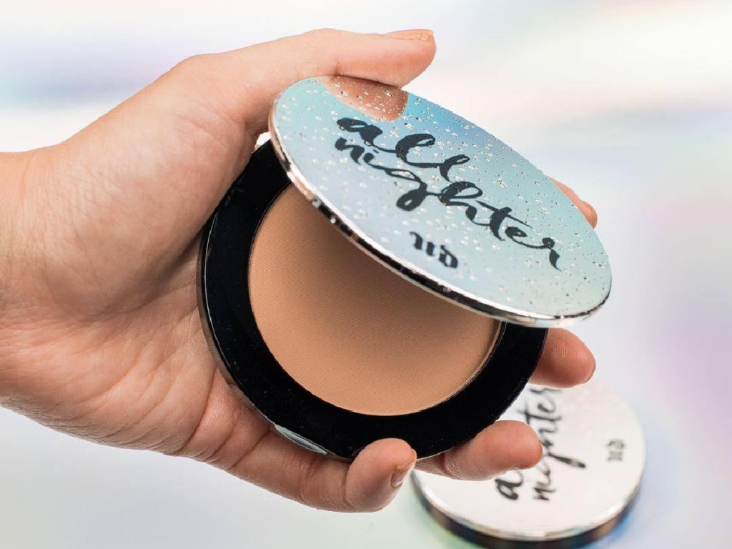 hand holding partically opened compact of Urban Decay All Night Waterproof Setting Powder