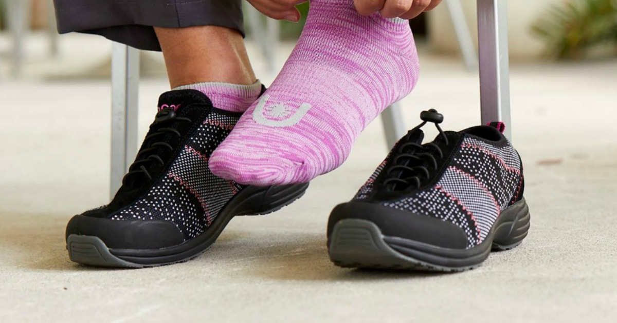 Woman wearing pink socks and putting on black and pink shoes
