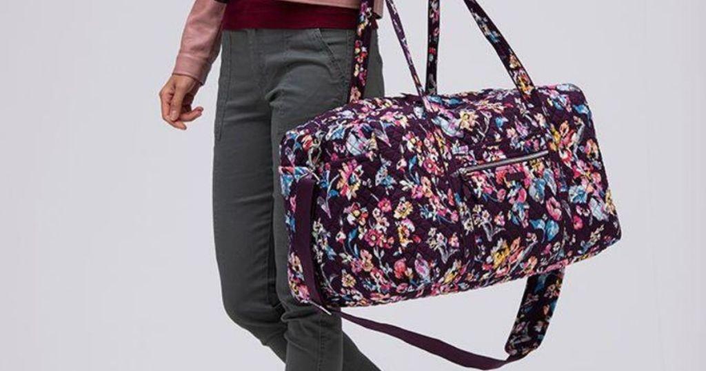 woman carrying a duffel bag