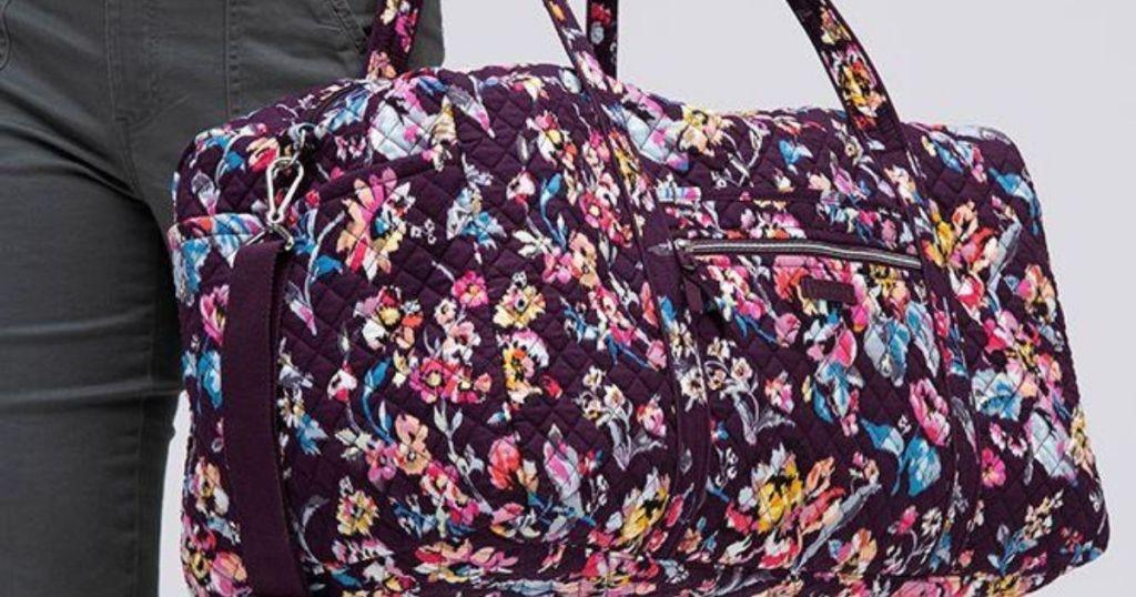 woman carrying a Vera Bradley duffel bag
