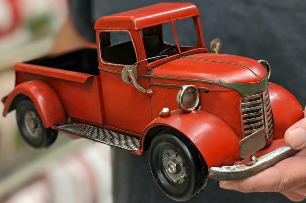 man holding vintage red truck decor