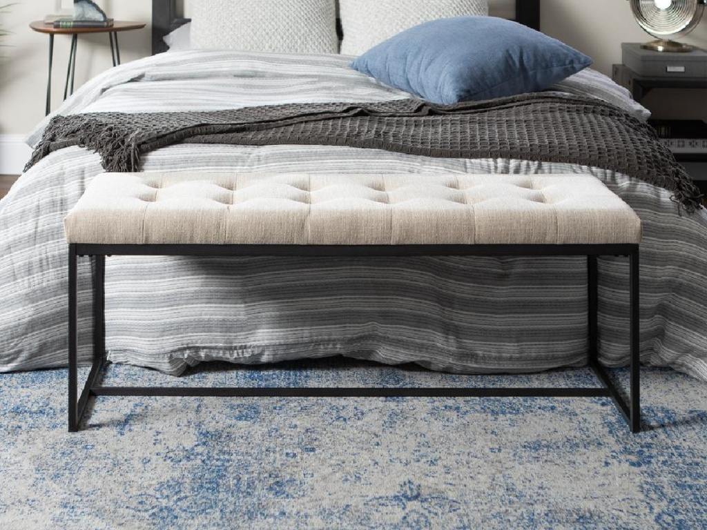 upholstered bench in front of bed