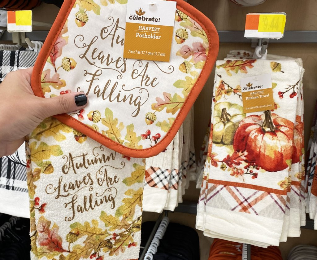 person holding up a matching pot holder and dish towel that say autumn leaves are falling