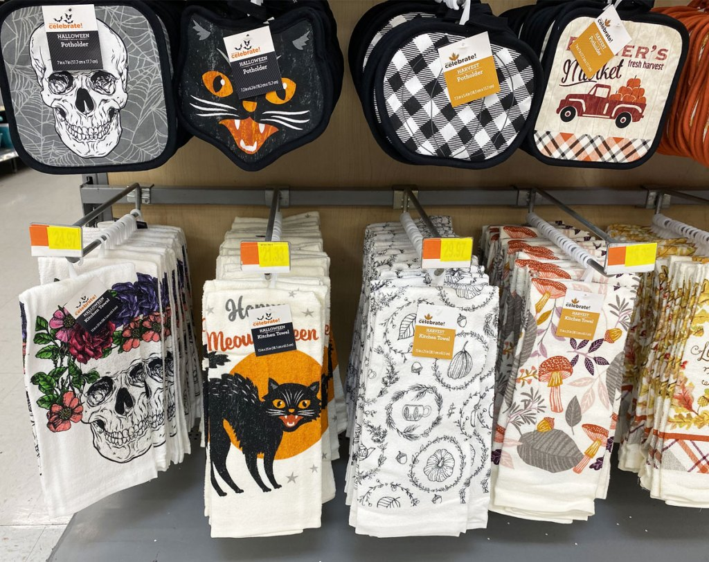 display of fall and halloween themed pot holders and matching dish towels