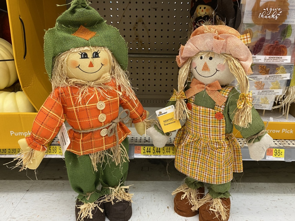 2 small scarecrows standing next to each other in store at walmart