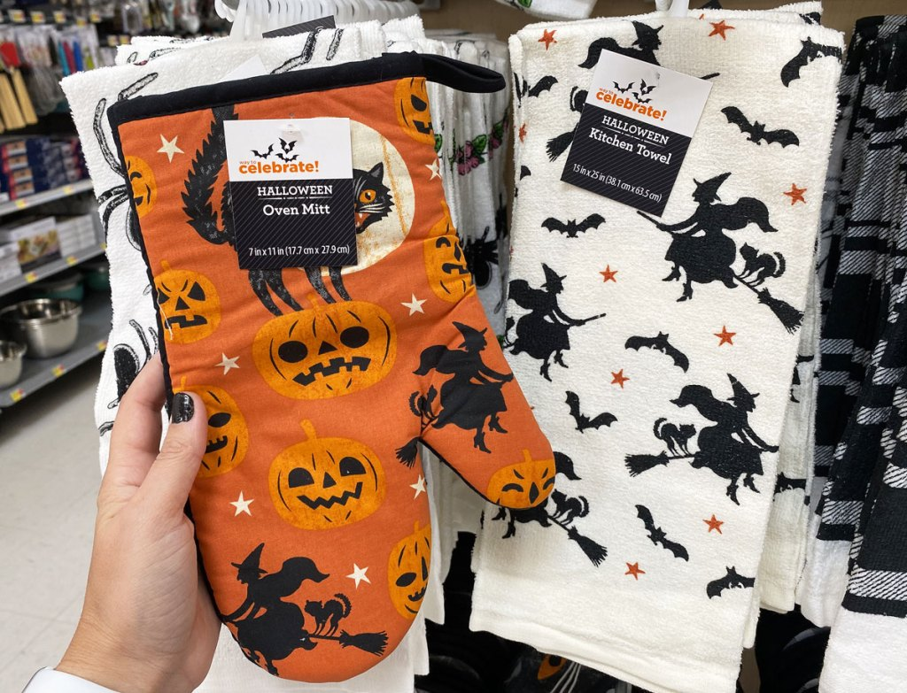 person holding orange oven mit with pumpkins and witches print and white dish towel with witches print