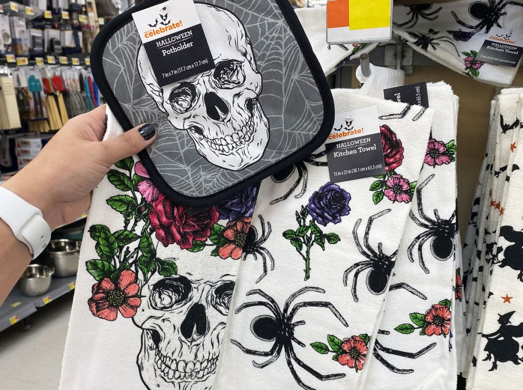 person holding up grey pot holder with a skull print and two white dish towels with skulls and spider prints