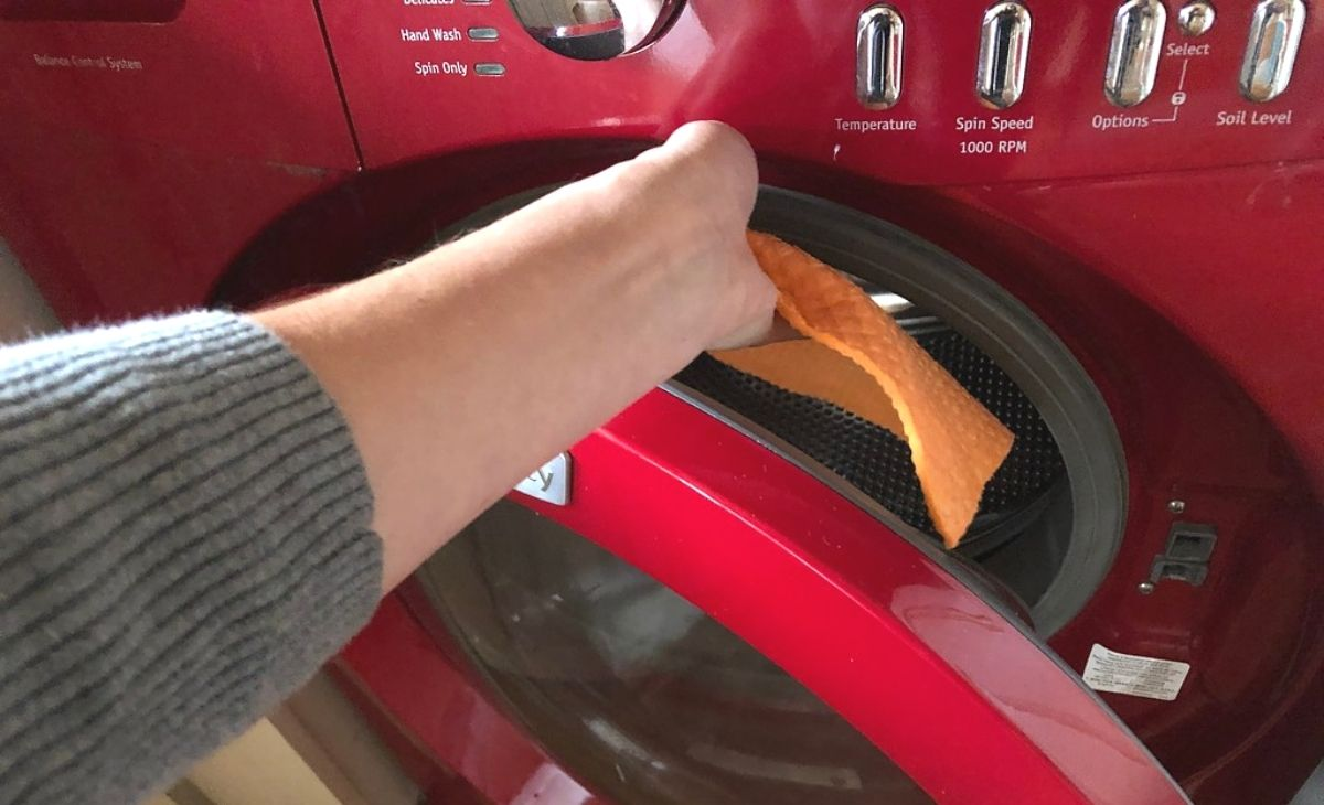 A hand placing a cloth in the washing machine
