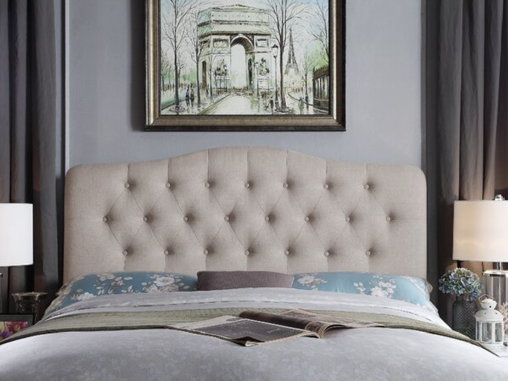 ivory tufted head board on a made up bed next to two lamps with a photo on the wall
