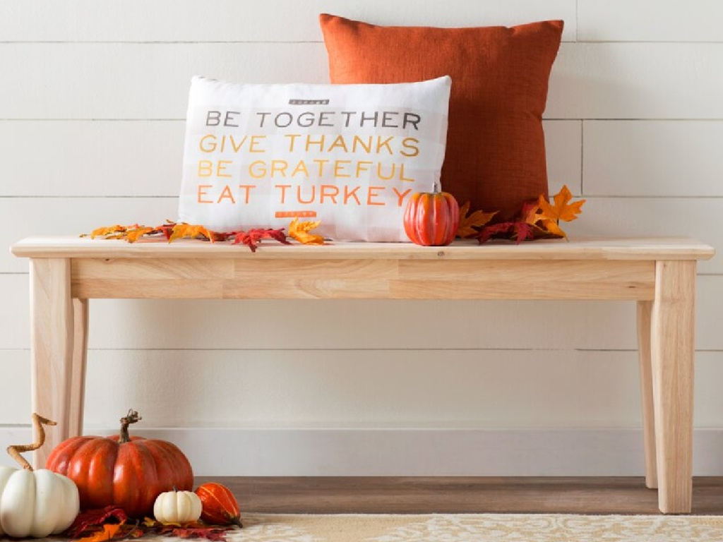 rustic wooden bench with fall pillows and pumpkins