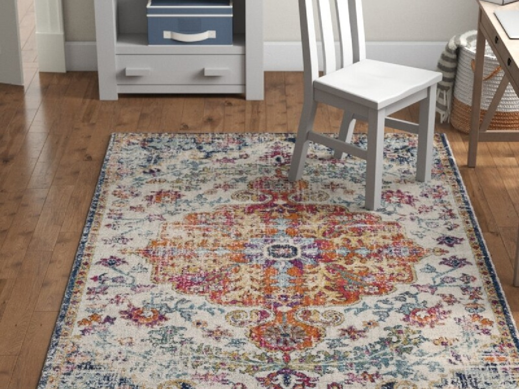area rug on the floor in an office with a white chair and stand