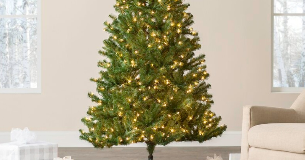 white lighted christmas tree in a living space with presents at the bottom