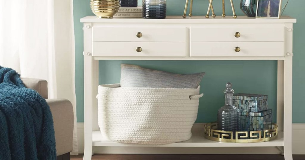 white console table with large white fabric basket on lower shelf