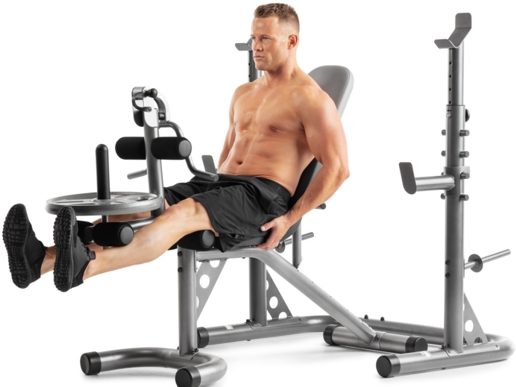 man sitting on a workout bench doing leg presses