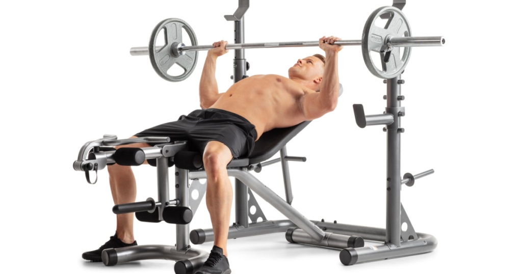 man laying down on a workout bench bench pressing large weights