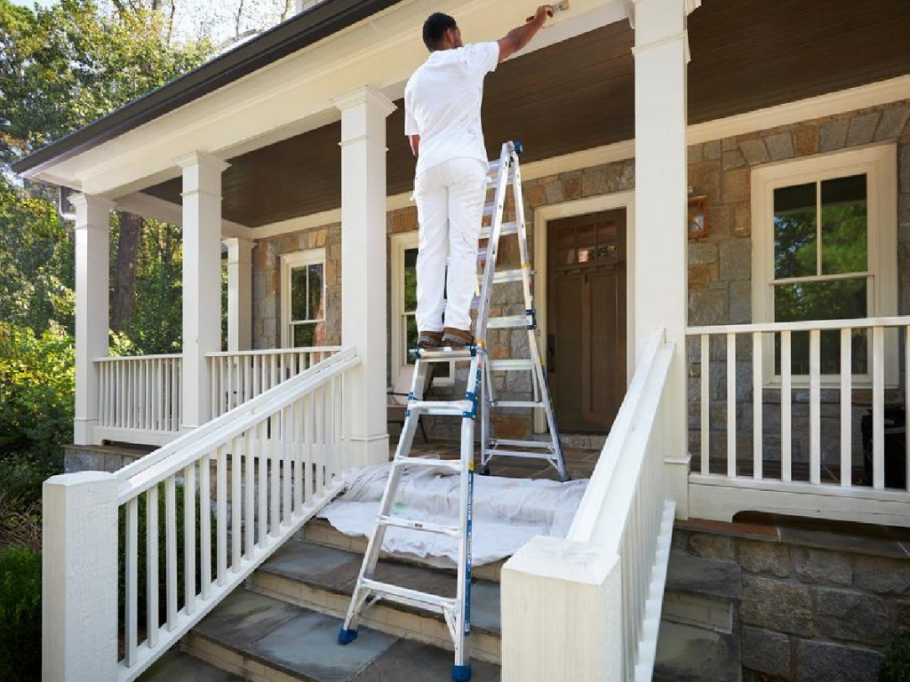 man on ladder painting outside of house