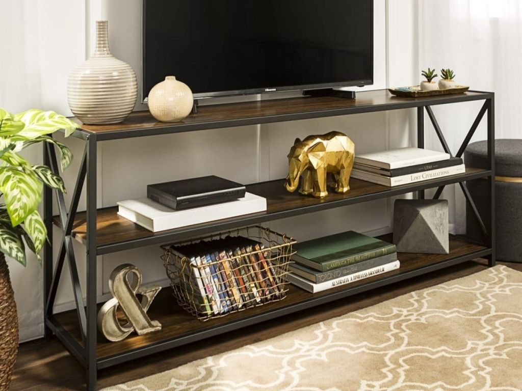 brown Wide X-Frame Metal & Wood Storage Shelf with tv and items on it