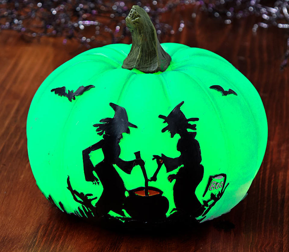 green pumpkin with witches on it