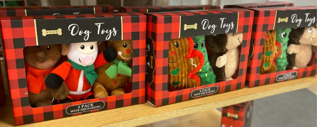 packs of three holiday dog plush toys on store table