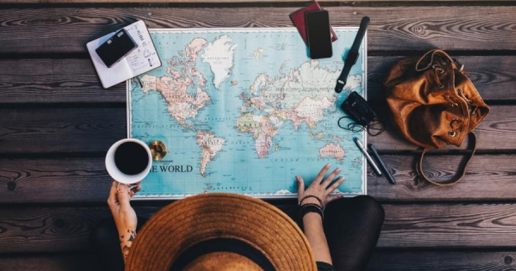 person wearing brown hat looking down at paper world map with cup of coffee