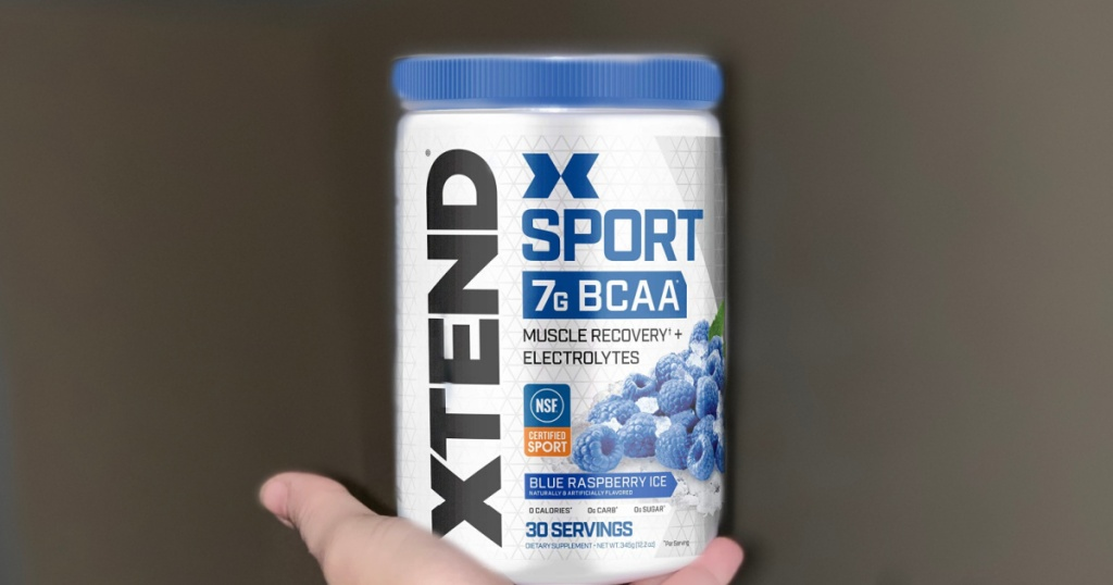 hand holding bottle of XTEND Sport BCAA Muscle Recovery + Electrolyte Powder in Blue Raspberry Ice 30-Servings