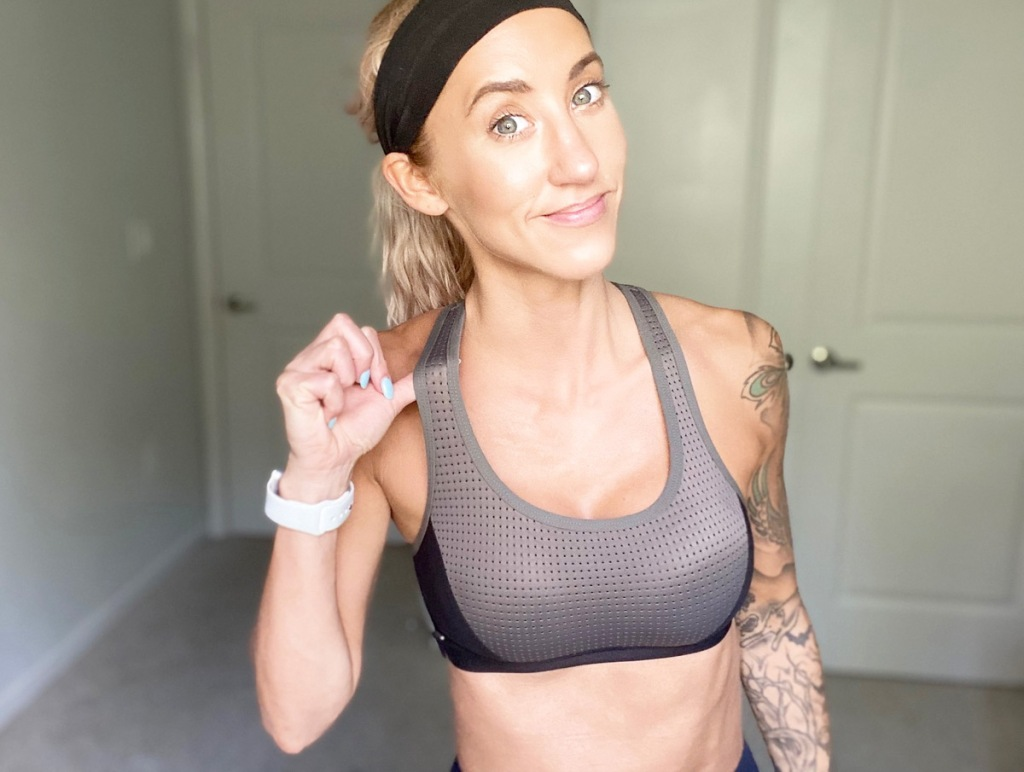 woman standing in bedroom wearing a grey and black sports bra and black headband