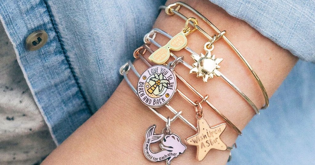 woman wearing denim jacket and multiple alex and ani bracelets with beach and mermaid themed charms