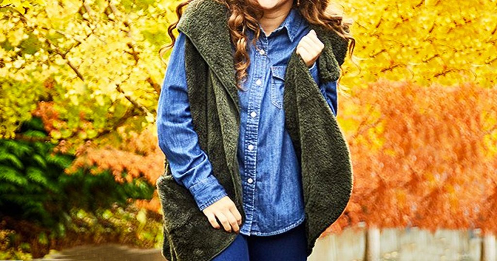 woman wearing denim long sleeve shirt with green faux fur hooded vest over it