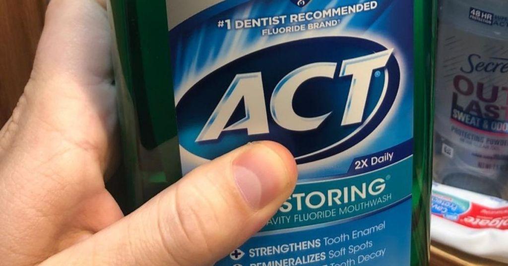 Hand holding ACT mouthwash