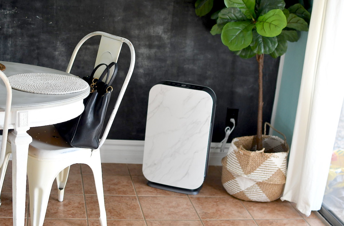 white alen air purifier sitting on tile floor next to plant