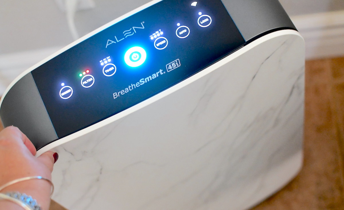 hand touching top of alen air purifier with lights on