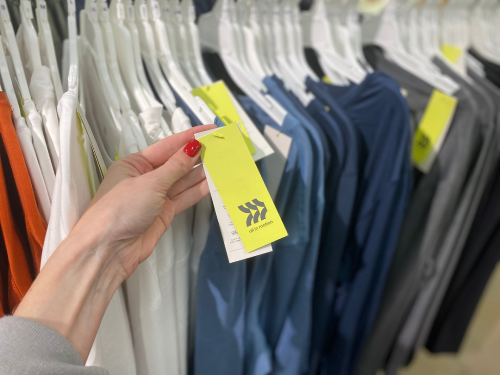 hand holding tag by shirts in store