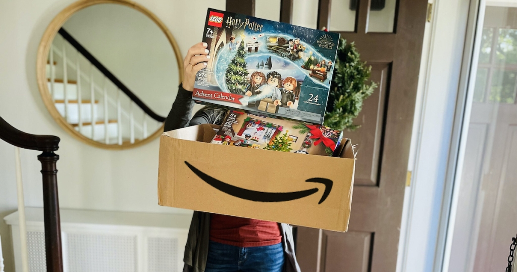 woman holding up amazon box with lego advent calendars inside