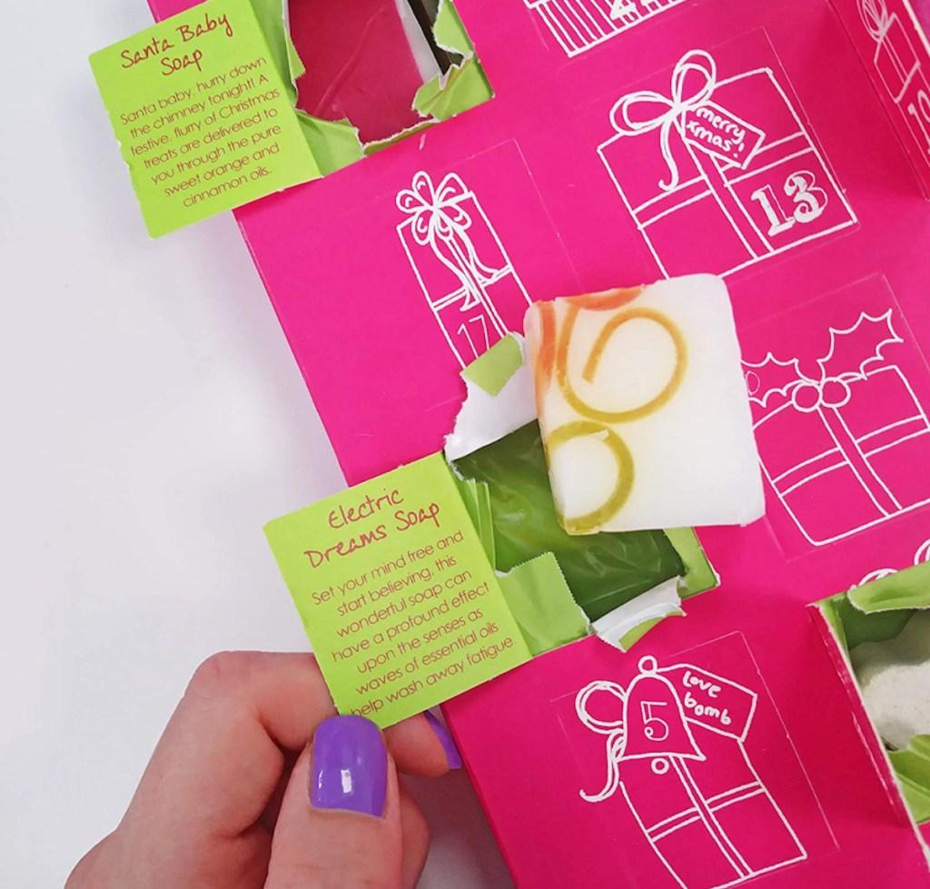 hand holding open door on advent calendar with soaps